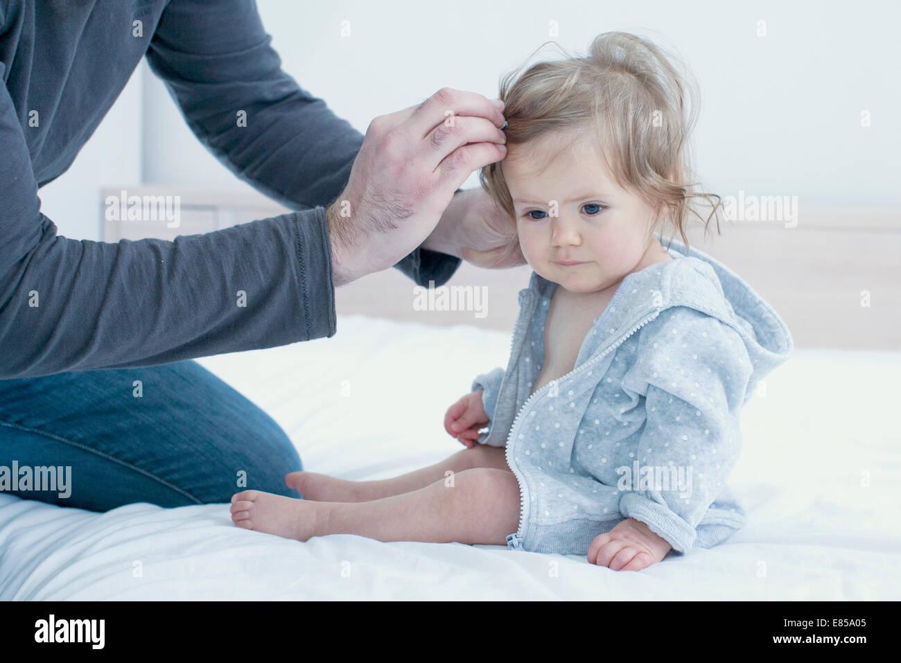 Il padre del bambino di fissaggio ai capelli della ragazza, ritagliato Immagini Stock