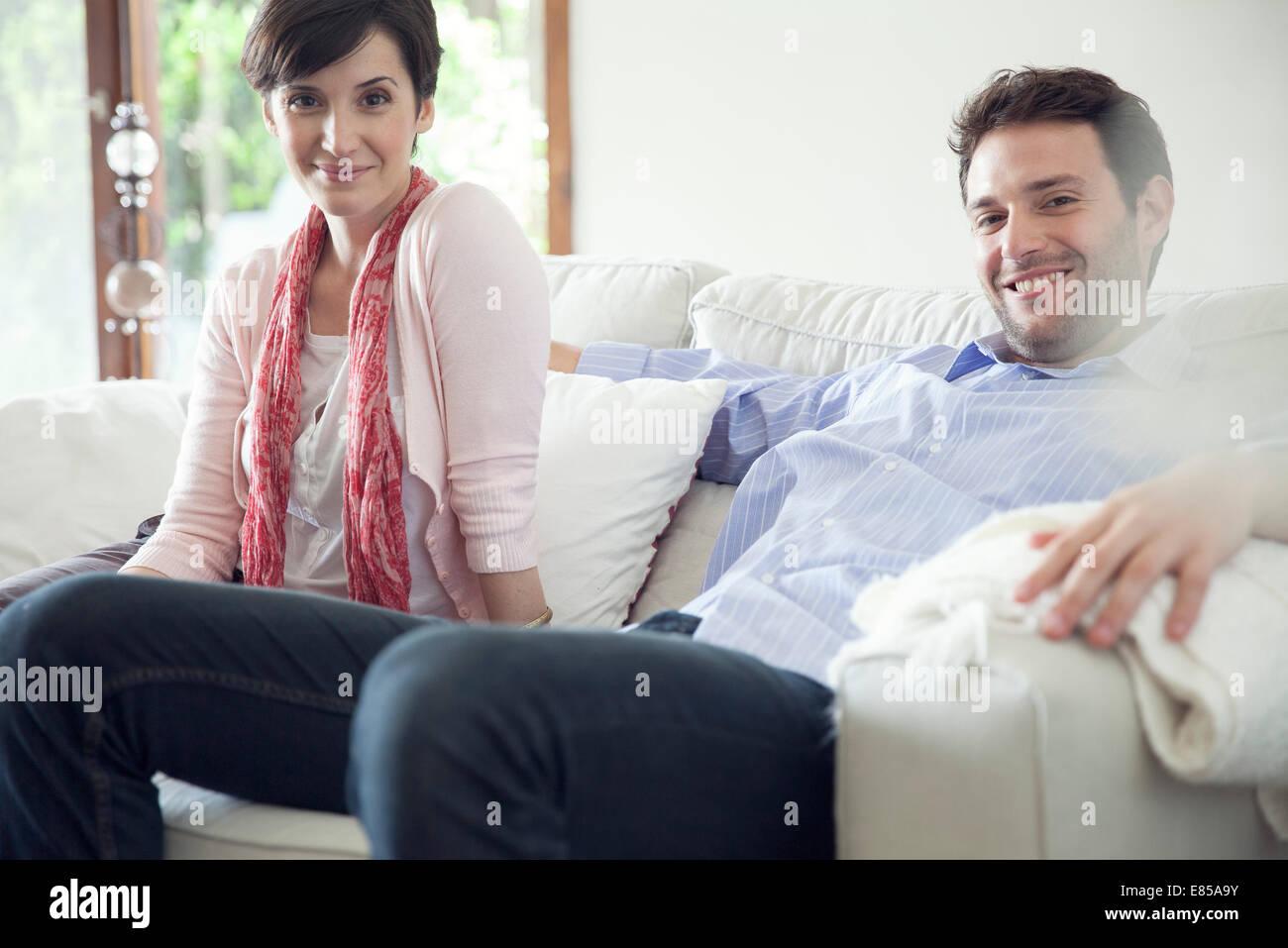 Giovane rilassante sul divano di casa Immagini Stock