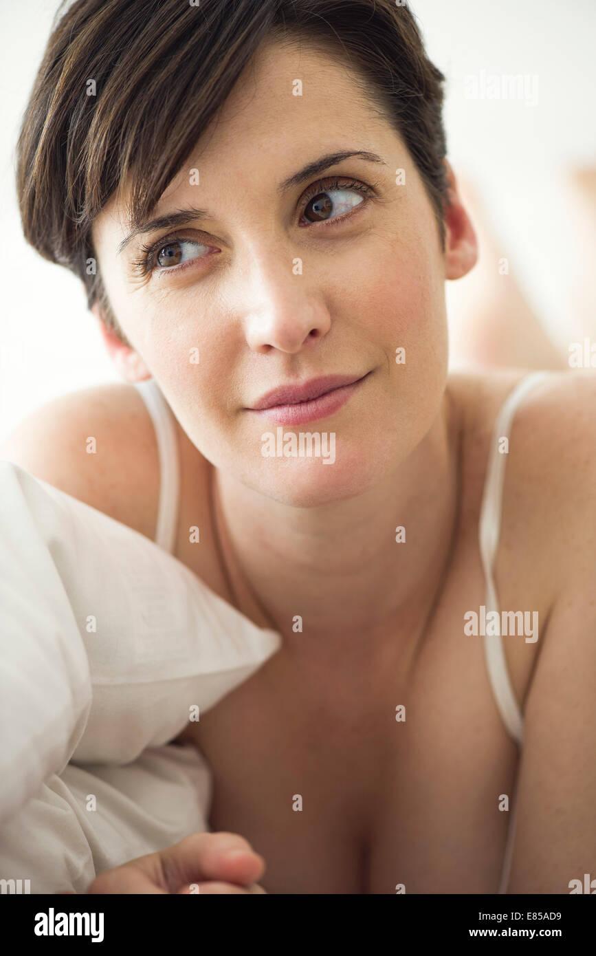 Donna sdraiata sul letto contemplando il suo futuro privato Foto Stock