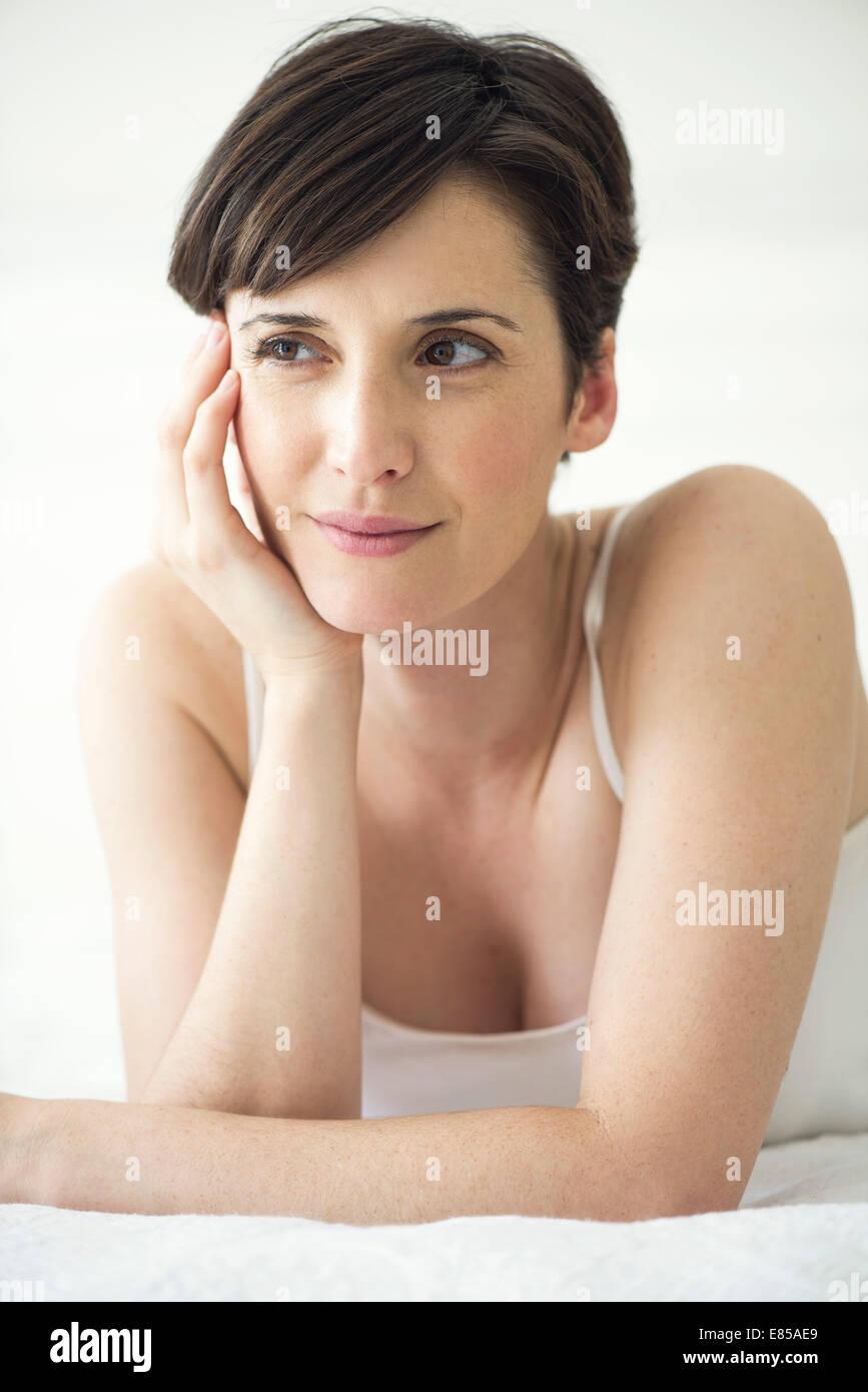 Donna sdraiata sul letto, ritratto Immagini Stock