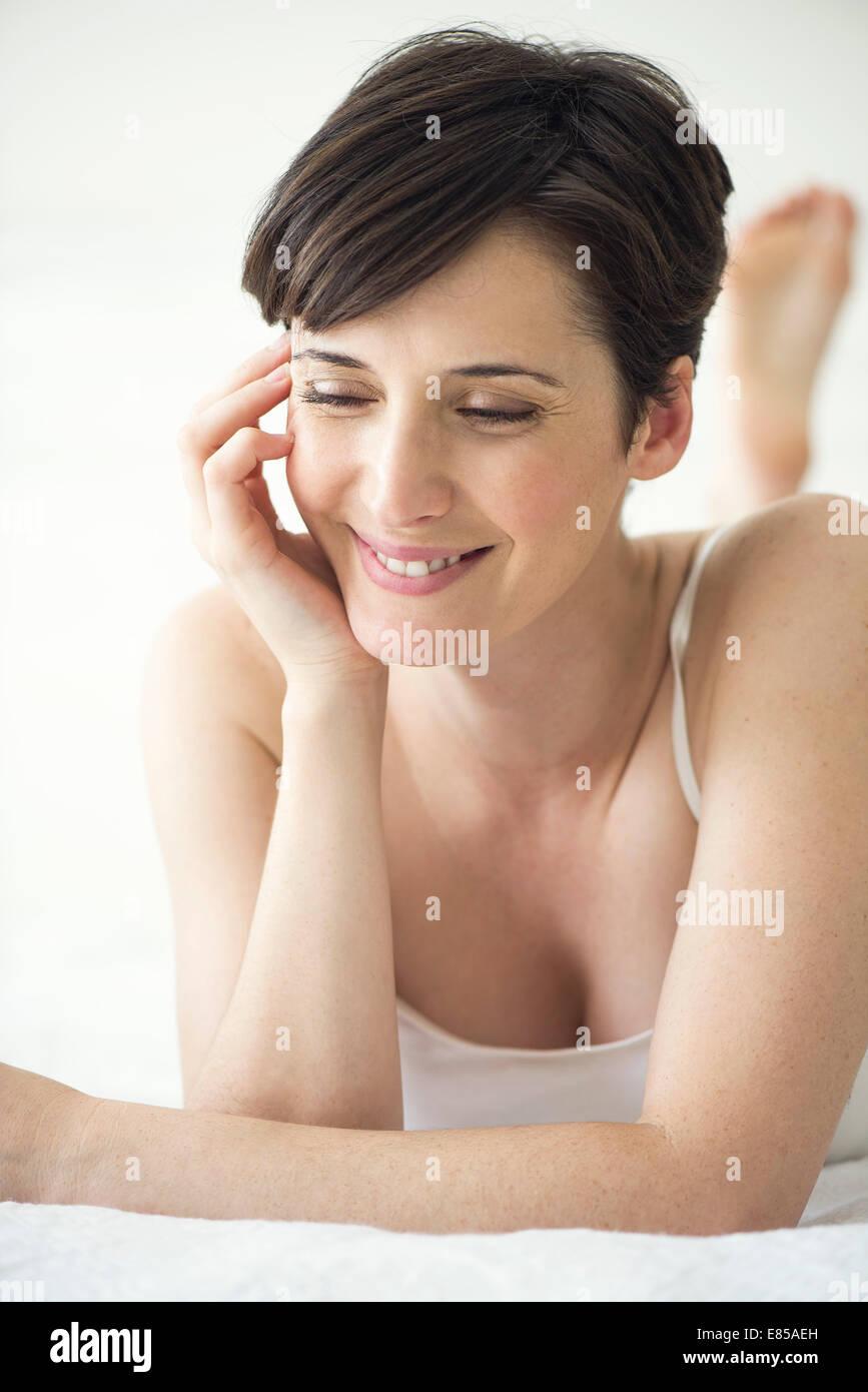 Donna sdraiata sul letto con aspetto di contentezza, ritratto Immagini Stock