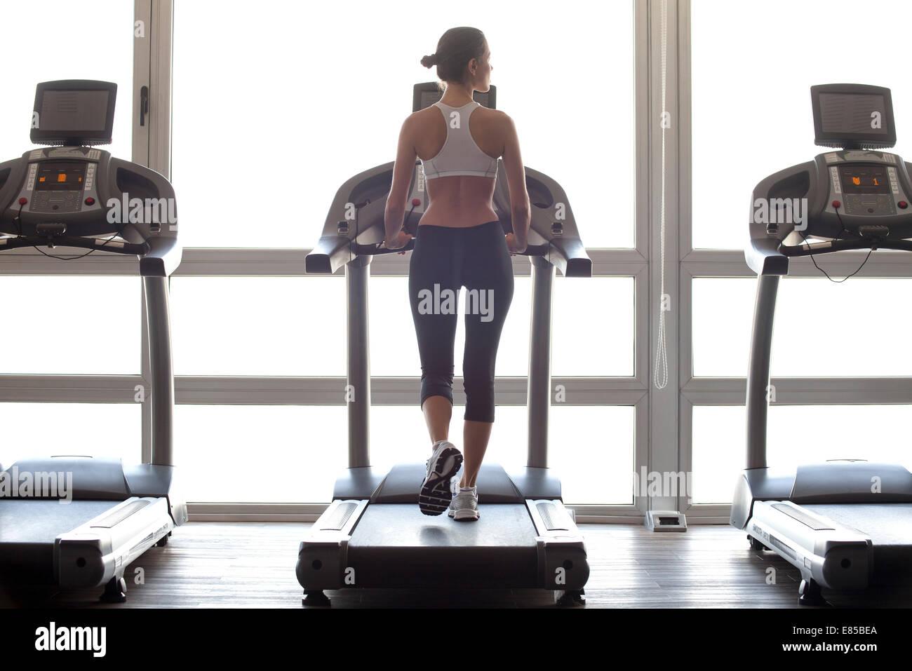 Donna di jogging sul tapis roulant in palestra Immagini Stock