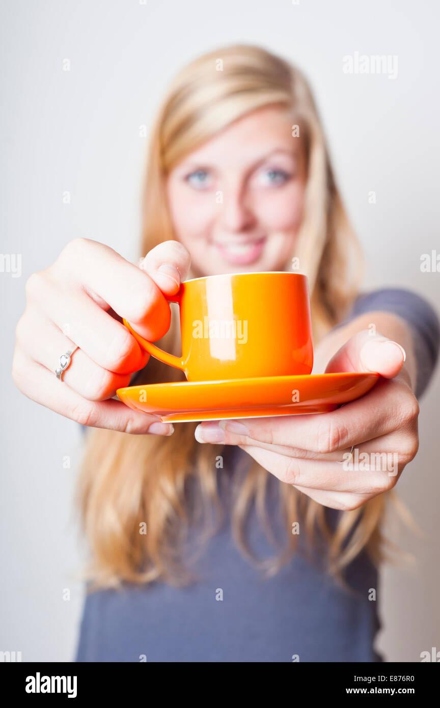 Adolescente bionda ragazza sorridente e offrendo una tazza di caffè Immagini Stock