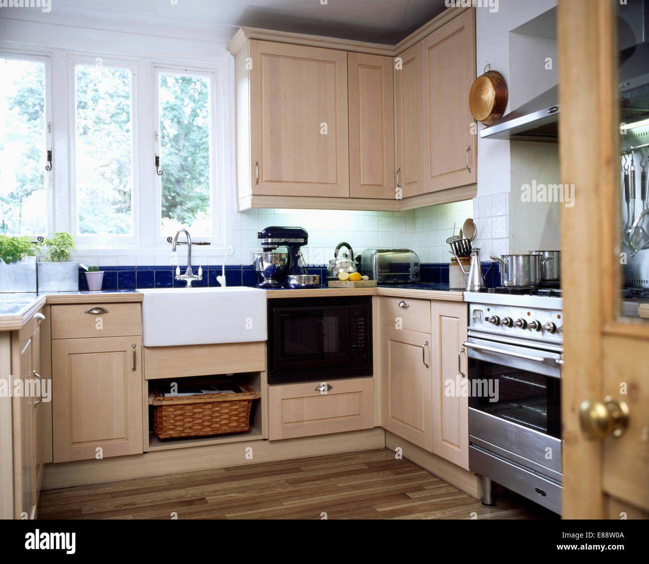 Belfast lavello sotto finestra nella cucina moderna con legno chiaro ...