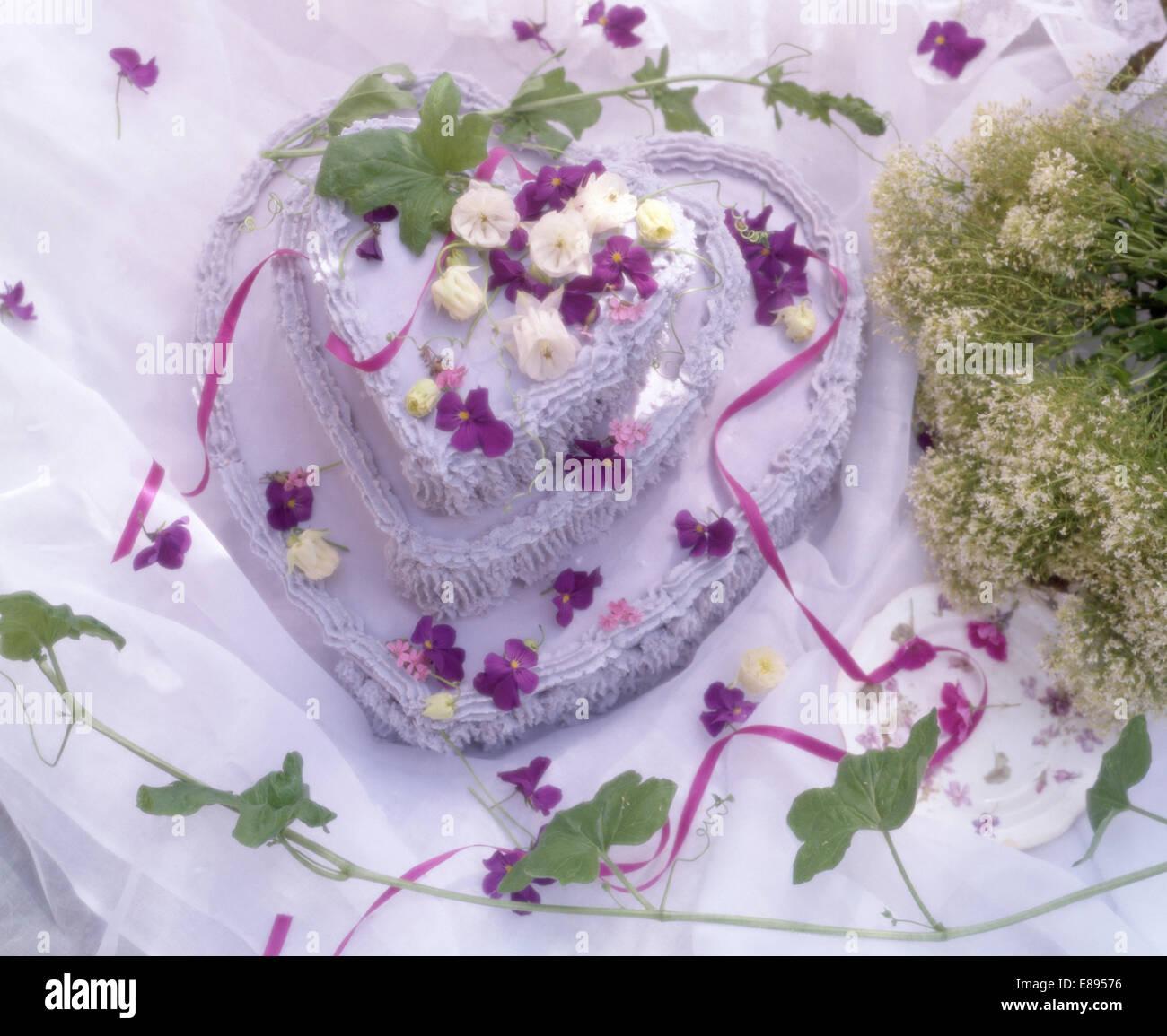 Still-Life di a forma di cuore di San Valentino torta decorata con viola mammola Immagini Stock