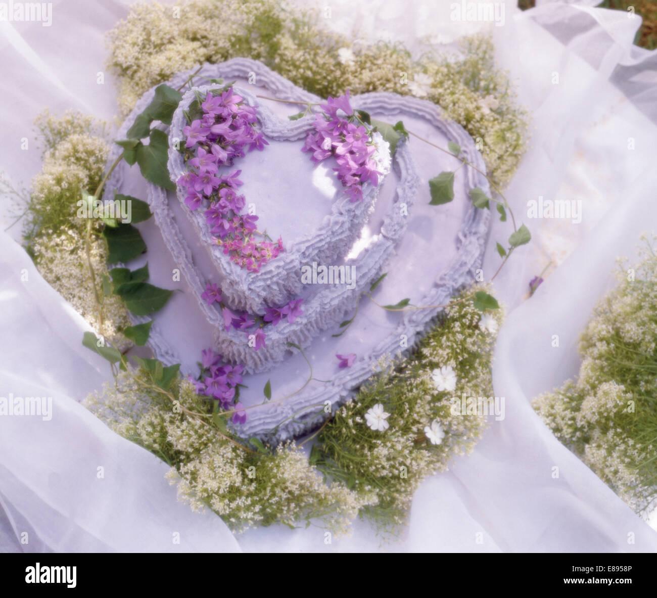 Still-Life di a forma di cuore di San Valentino torta decorata con malva e campanula gypsophila bianco Immagini Stock