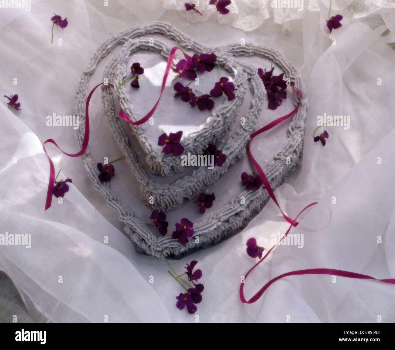 Still-Life del cuore a forma di torta di San Valentino decorate viola mammola Immagini Stock