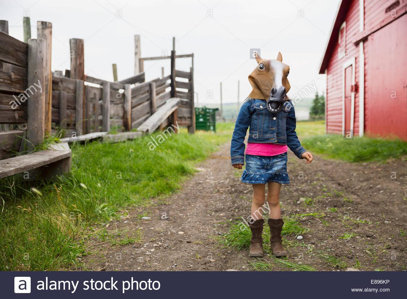 Ragazza che indossa la maschera di cavallo al di fuori di un fienile Immagini Stock