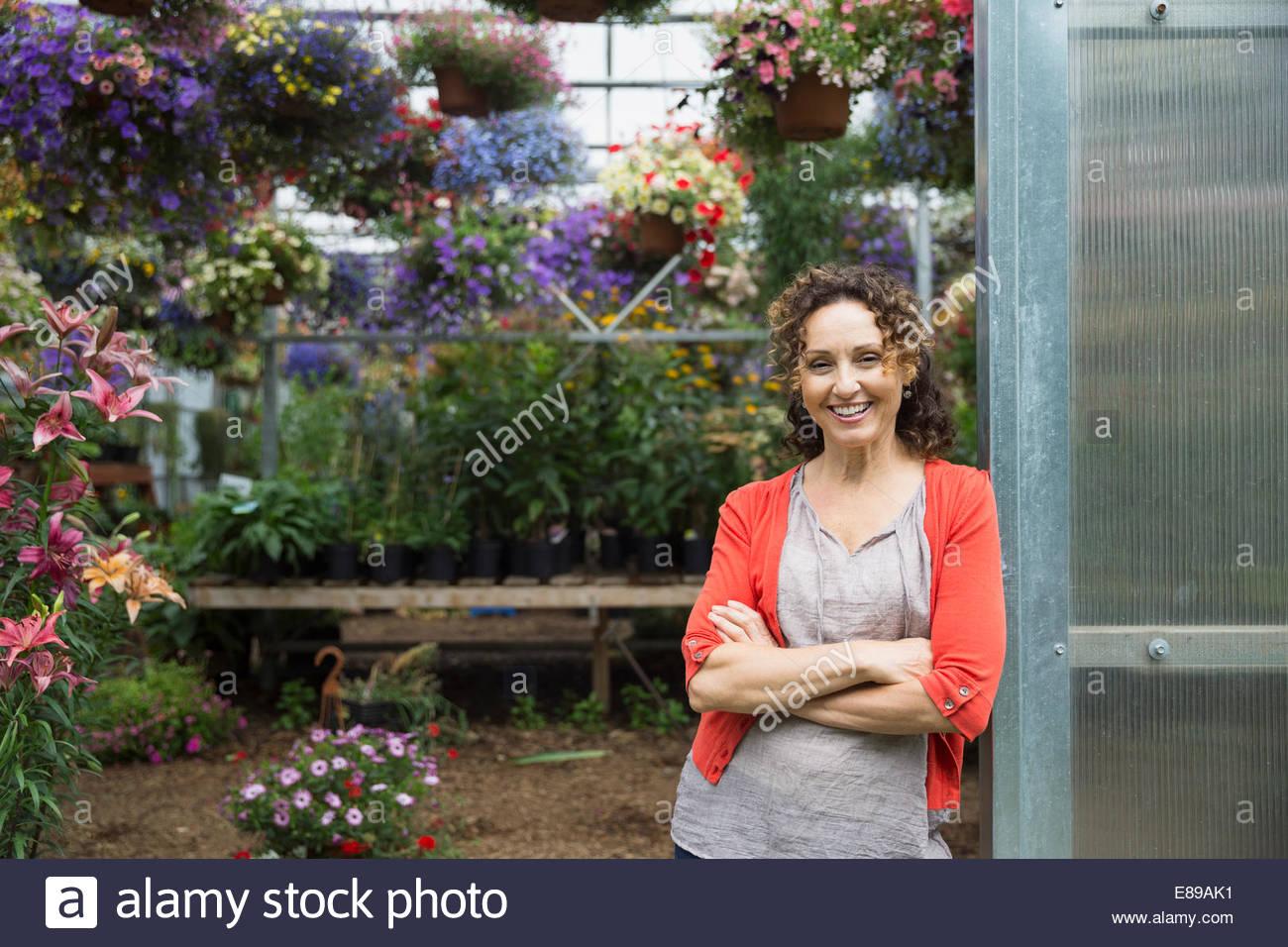 Fiducioso donna nella porta del vivaio di piante in serra Immagini Stock