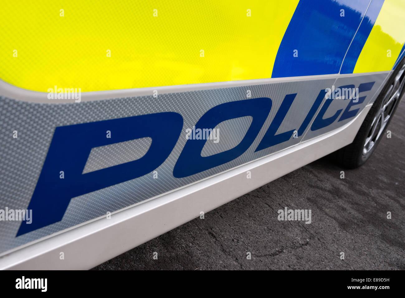 La polizia di parola su un segno riflettente sul lato di un bianco auto della polizia britannica Immagini Stock