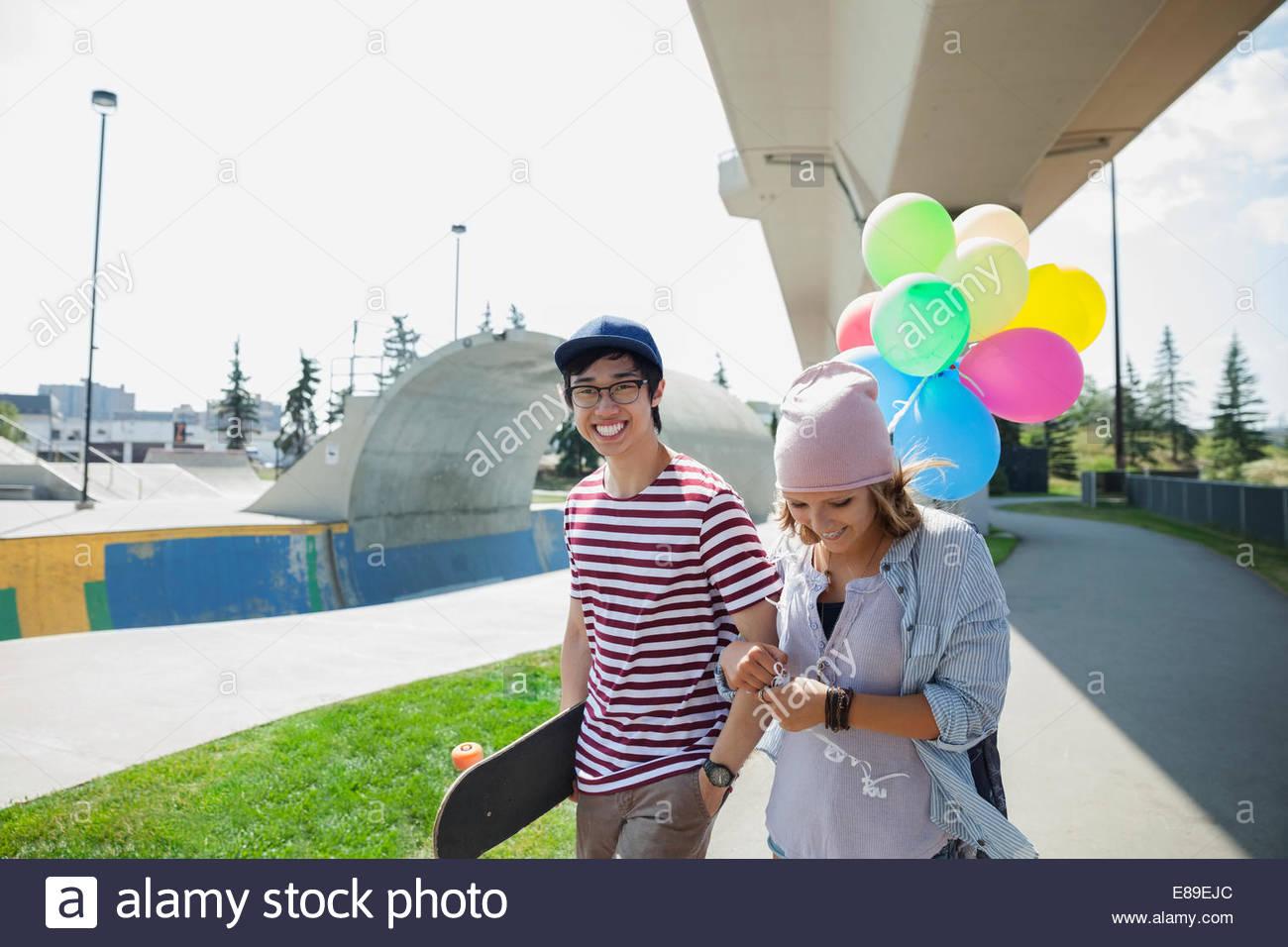 Giovane adolescente con palloncini a skate park Immagini Stock