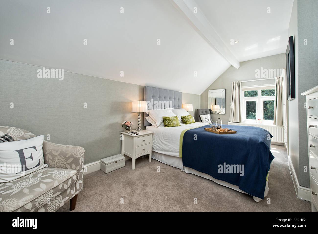 La prima colazione a letto in un contemporaneo confortevole camera matrimoniale arredata in colori blu e grigio Immagini Stock