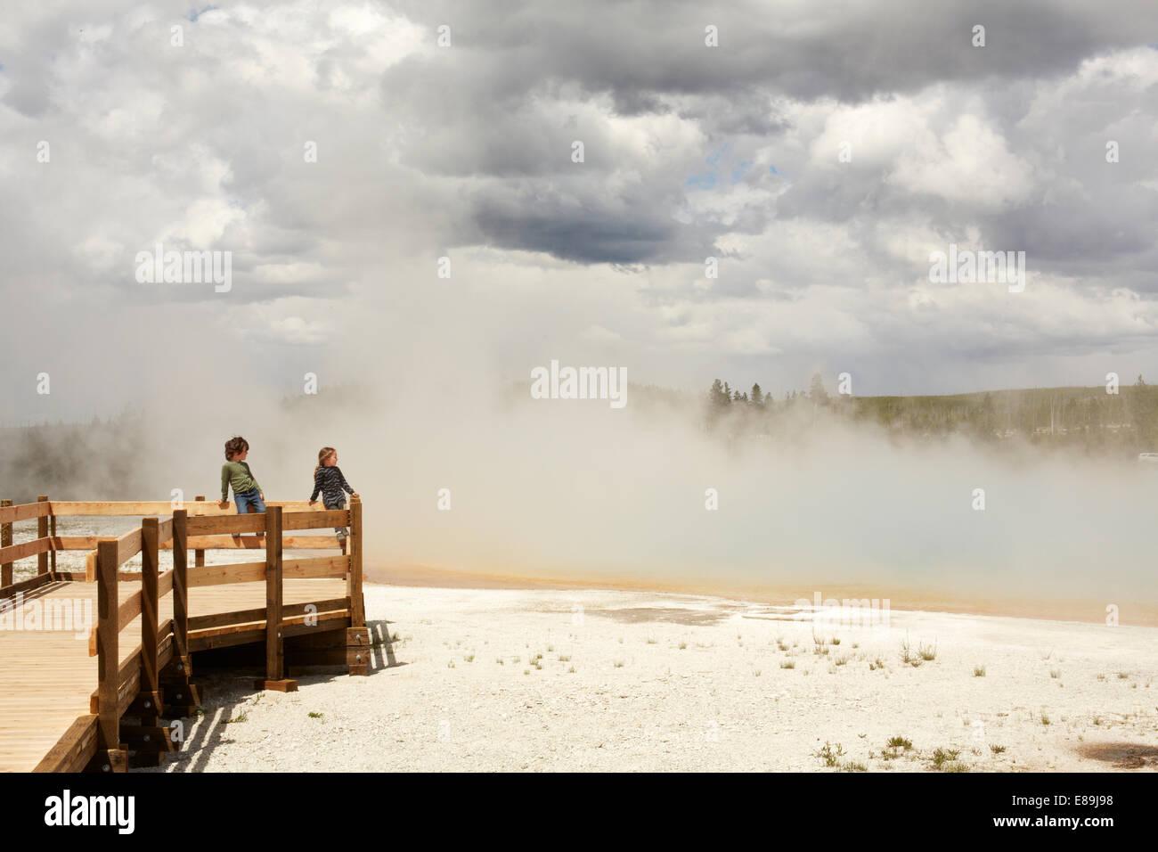I bambini guardando il geyser di Yellowstone Immagini Stock