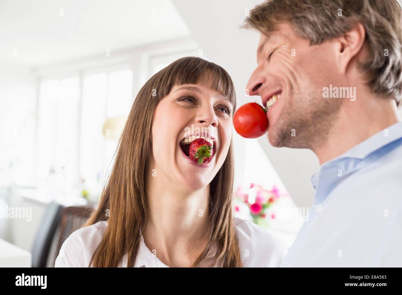 Coppia portando la fragola e il pomodoro in bocca Foto Stock