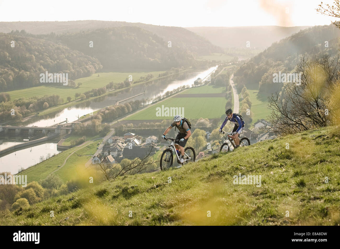Giovani uomini mountainbike al tramonto, Baviera, Germania Immagini Stock