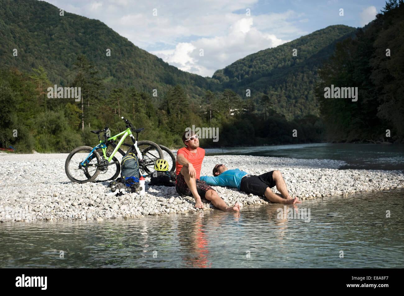 Due mountain bikers avente un riposo a Soca river, Tolmin, Istria, Slovenia Immagini Stock