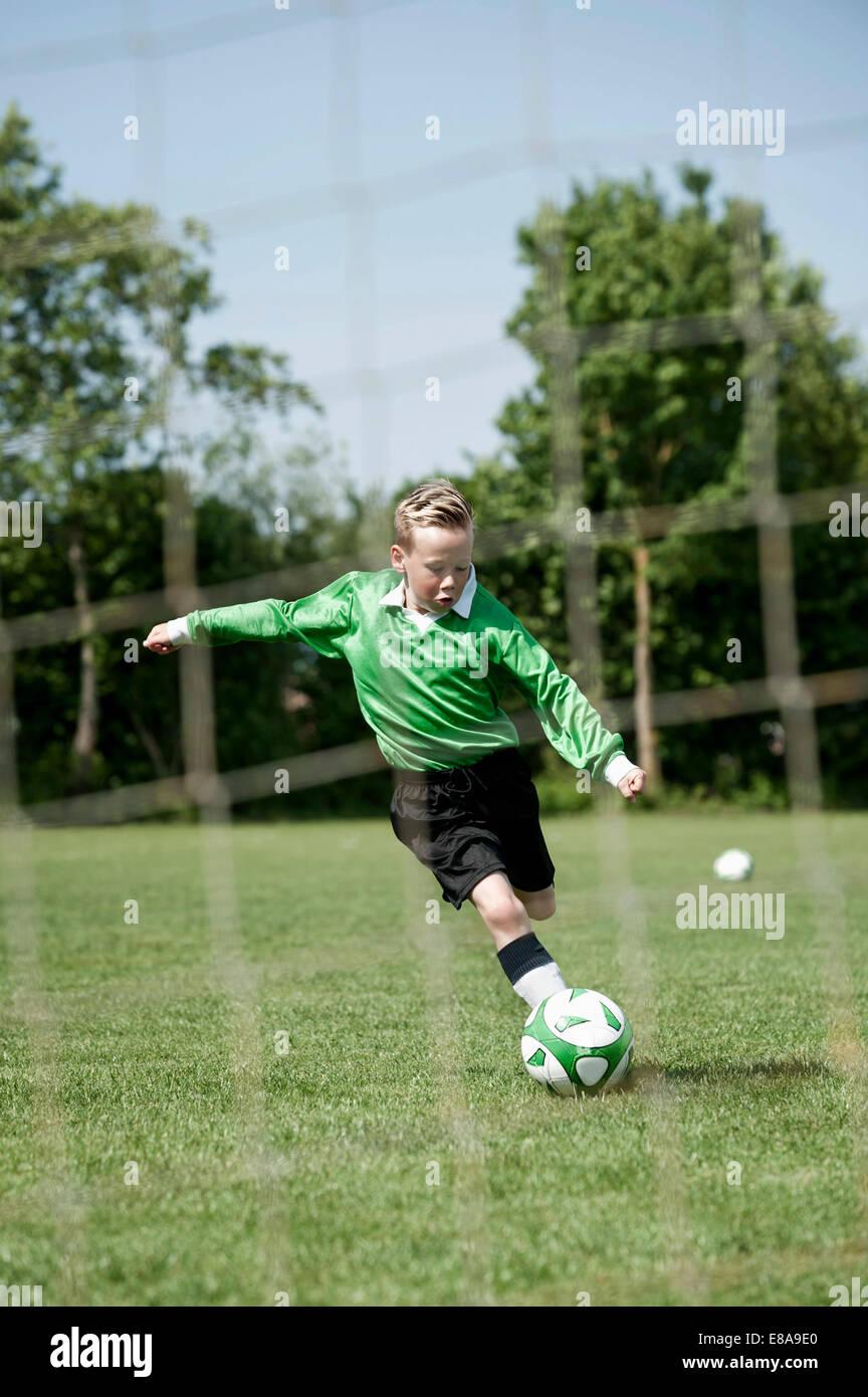 Ragazzo giovane soccer sanzione pratica sfera di calcio Immagini Stock