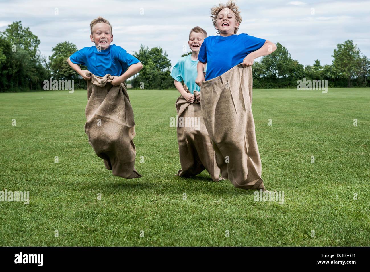 Tre giovani ragazzi in esecuzione in sackrace jumping Immagini Stock