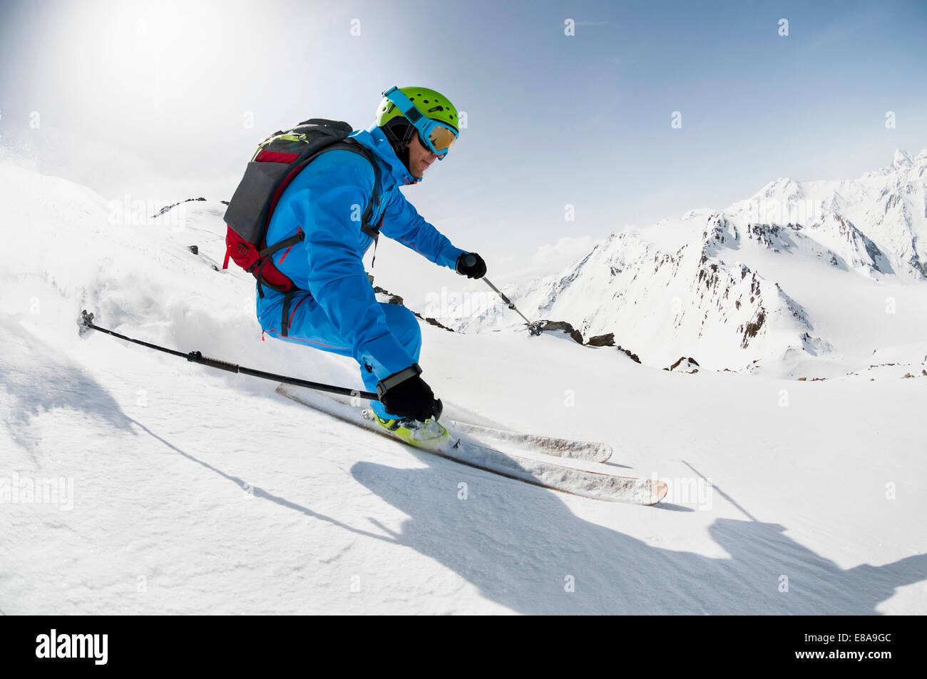 L'uomo sciatore sci discesa pendio ripido Alpi Immagini Stock