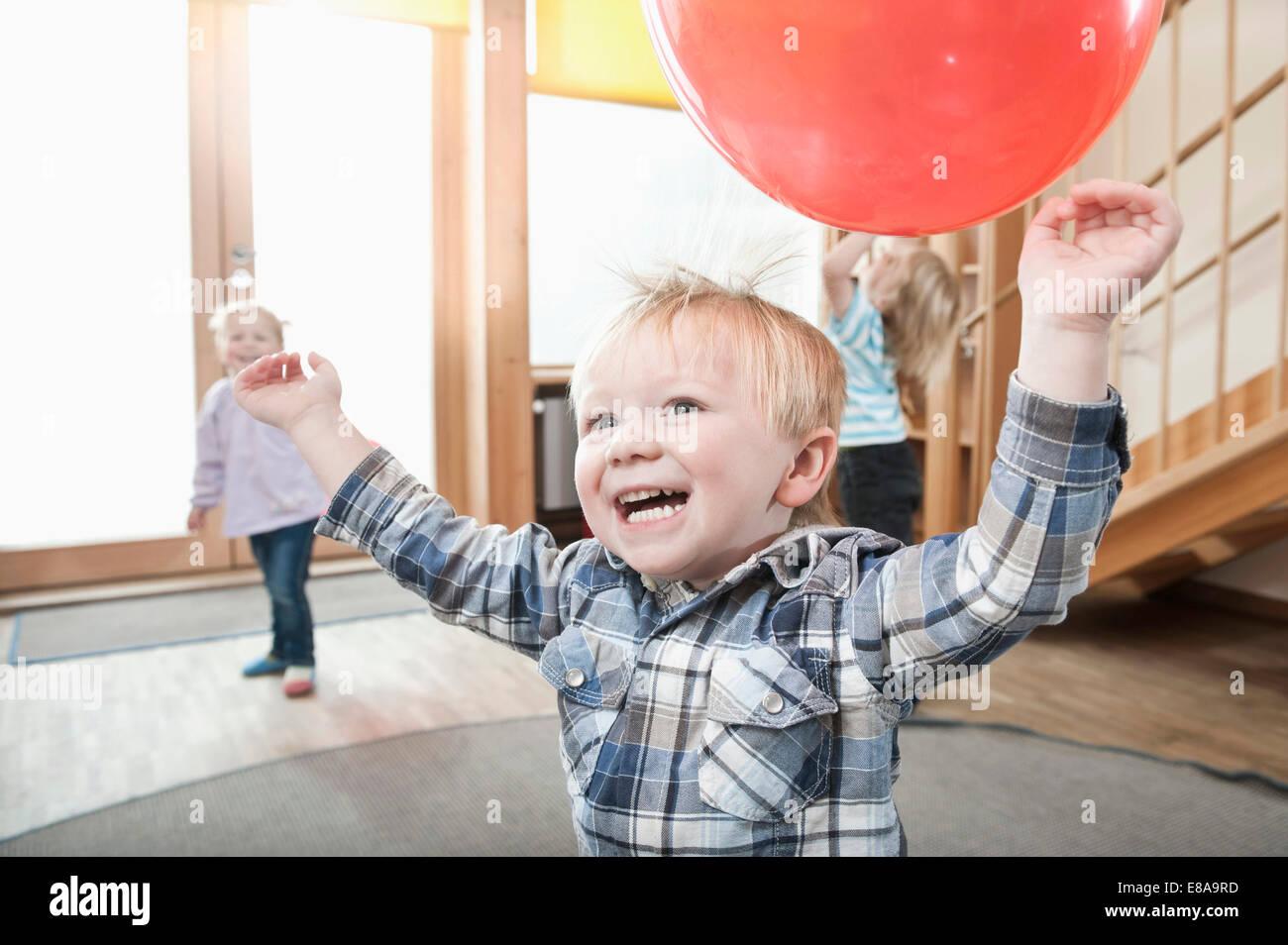 Bambini che giocano con palloncini rossi in kindergarten Foto Stock