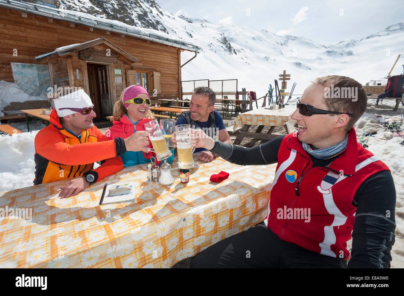 Gruppo cabina sciatori pranzo birra neve invernale Immagini Stock