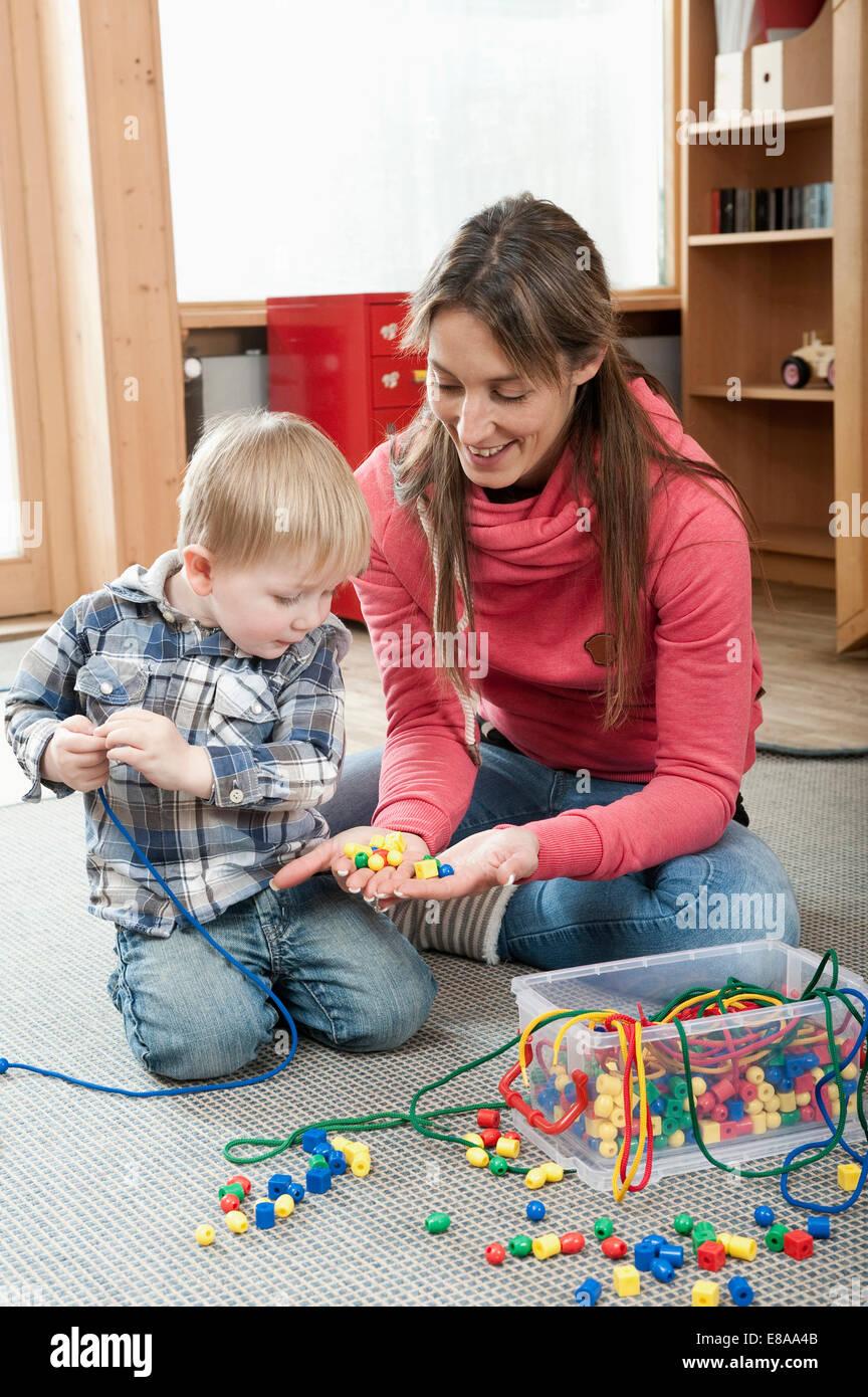Educatore femmina offrendo ragazzino di perls in legno per la realizzazione di una collana Immagini Stock