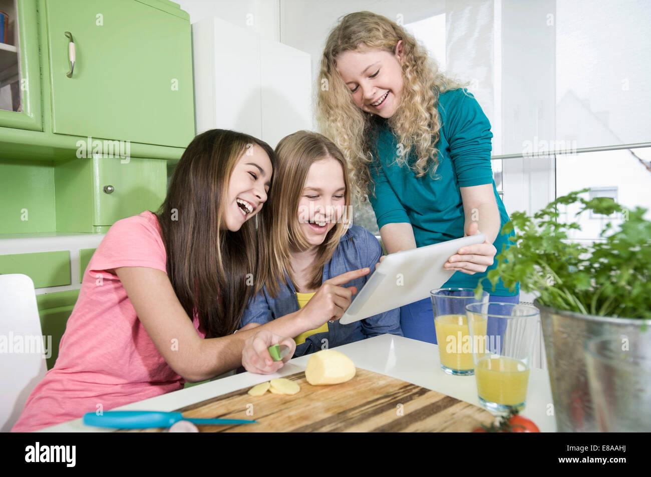 Ragazze in cucina con tavoletta digitale, preparare verdura Immagini Stock
