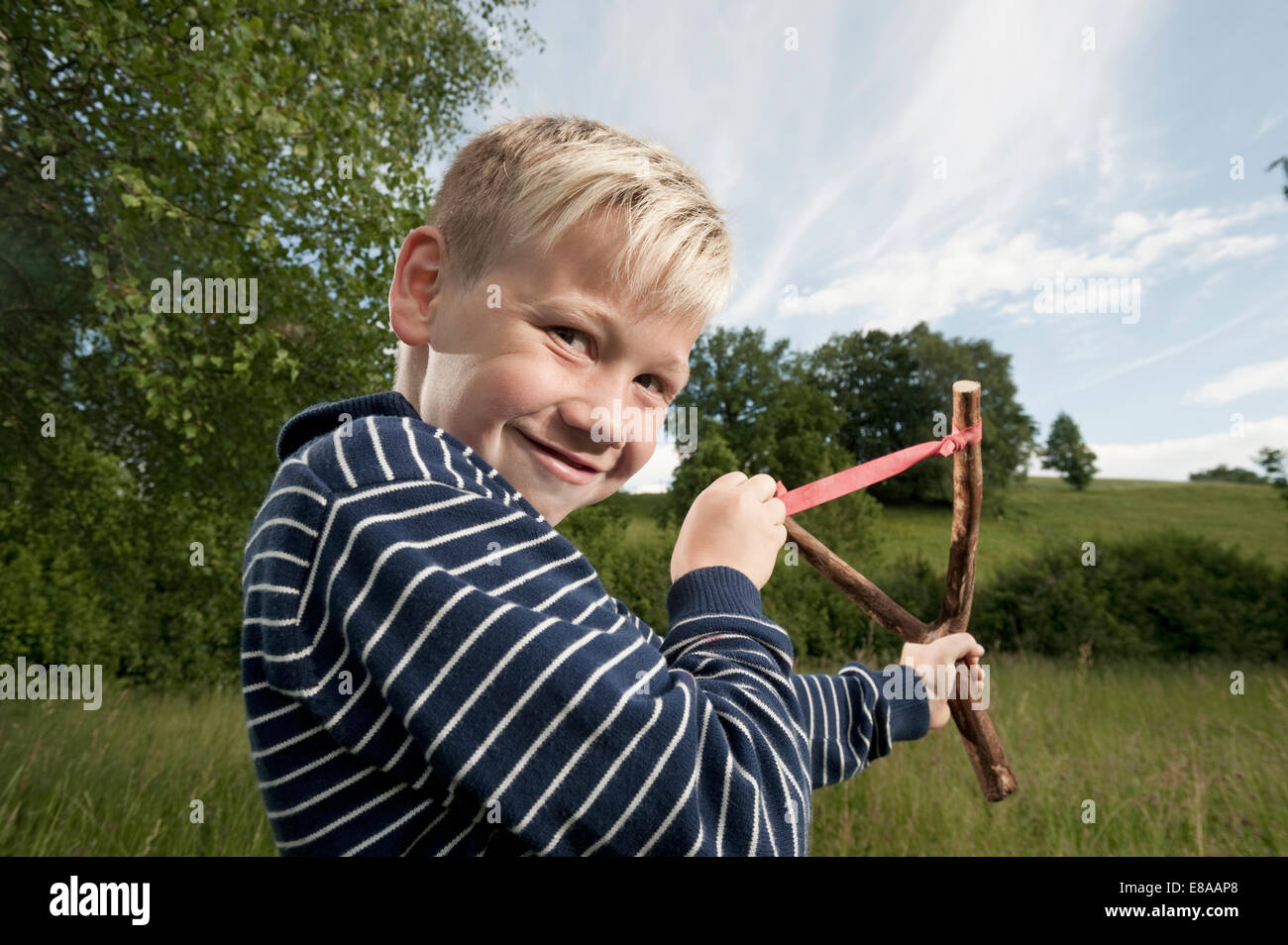 Cheeky giovane ragazzo biondo slingshot sorridente Immagini Stock