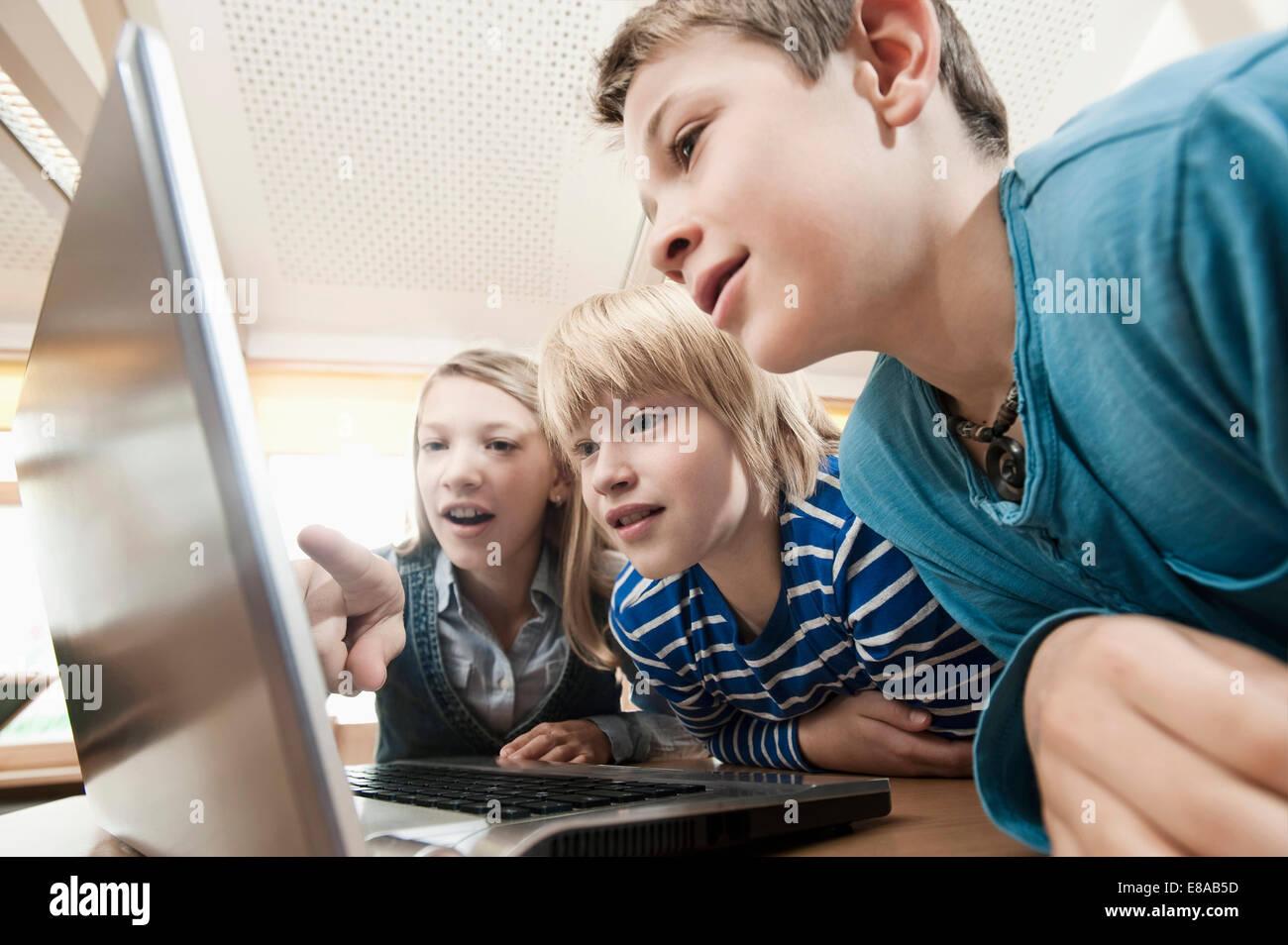 Tre bambini guardando al laptop Immagini Stock