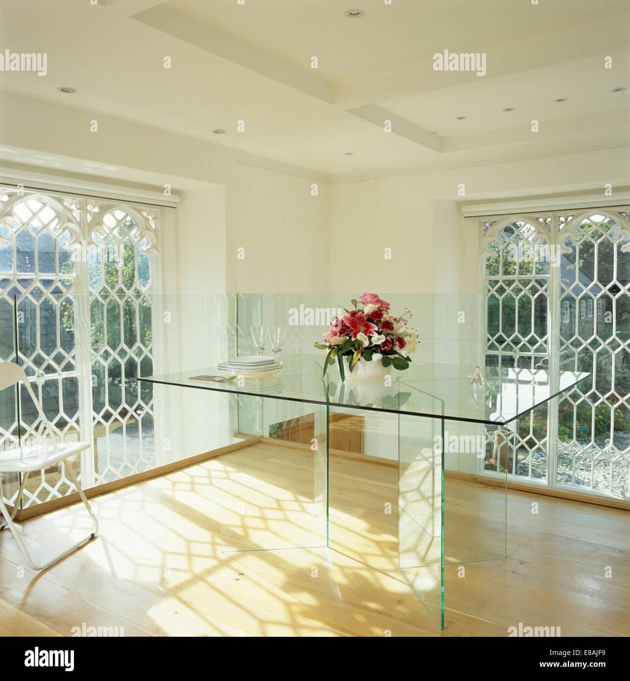 Tavolo di vetro e pavimenti in legno nella sala da pranzo moderna ...