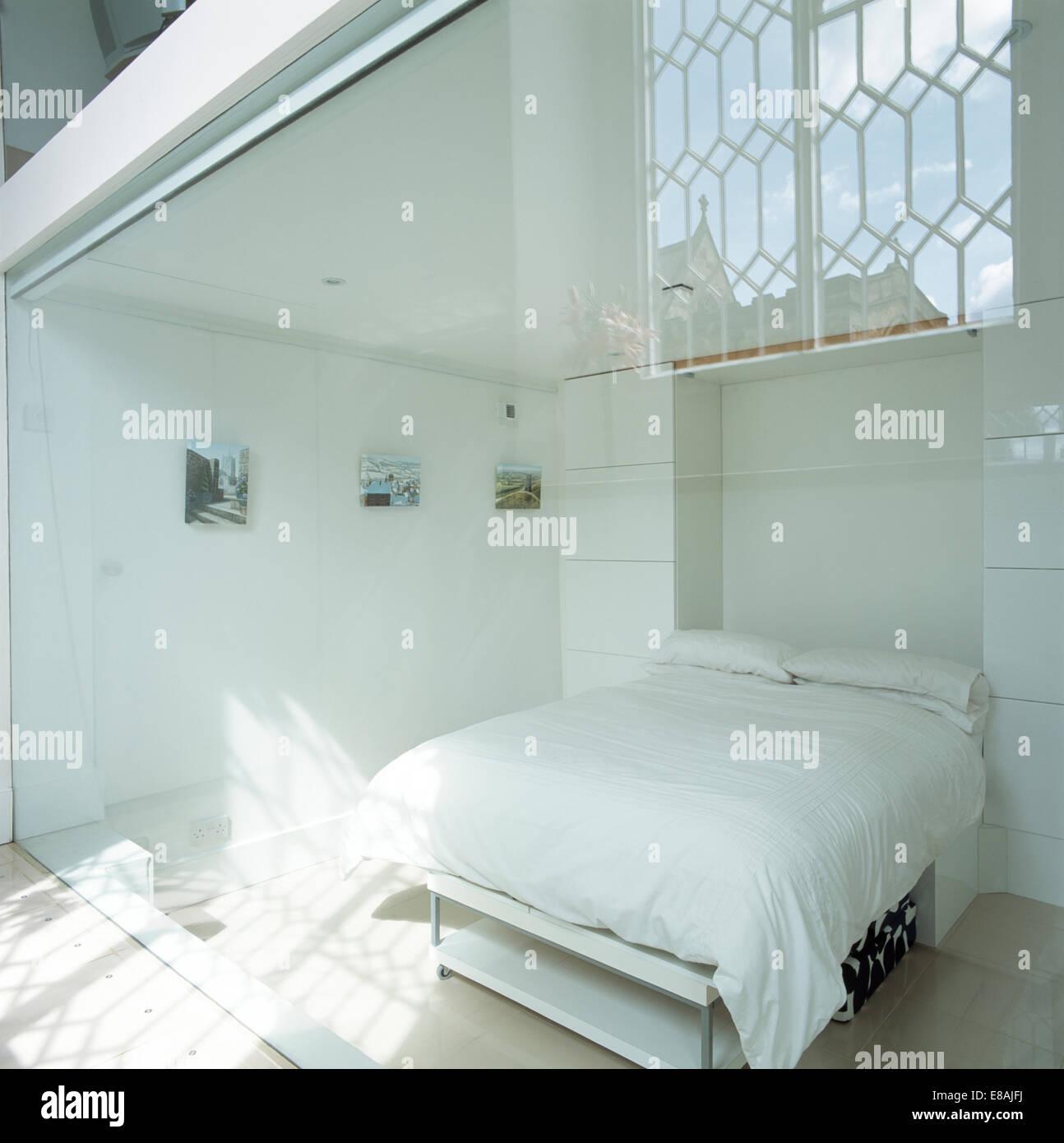White cuscini e piumoni sul letto in bianca e moderna camera da ...