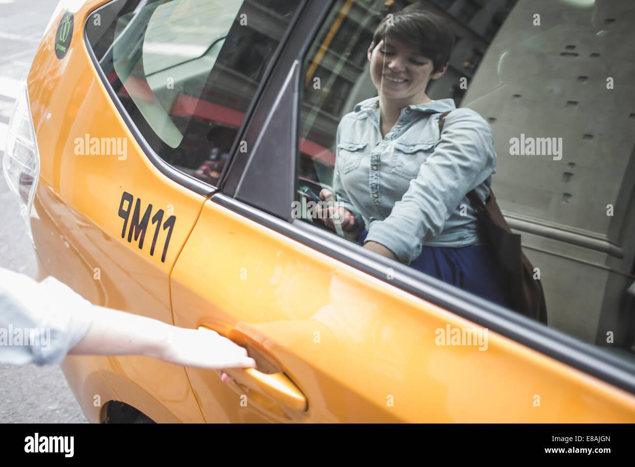 La donna per arrivare in taxi gialli, New York, US Immagini Stock