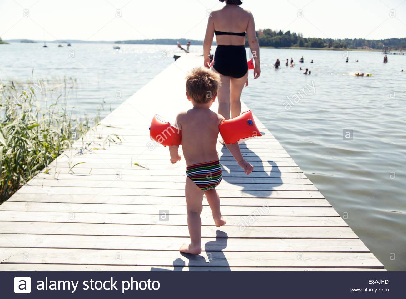 Vista posteriore del toddler maschio seguenti madre lungo il lago di pier Immagini Stock