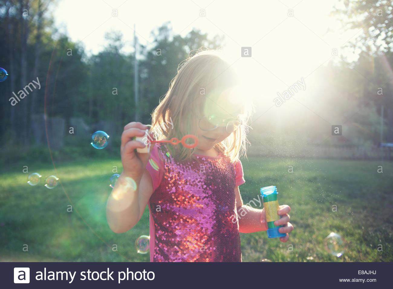 Ragazza a soffiare bolle in giardino Immagini Stock