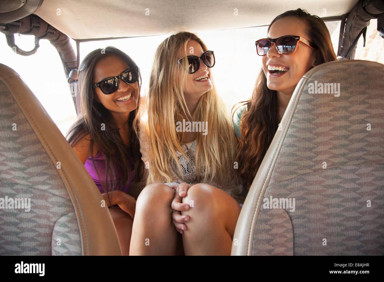 Tre giovani donne ridere nel sedile posteriore della macchina Immagini Stock