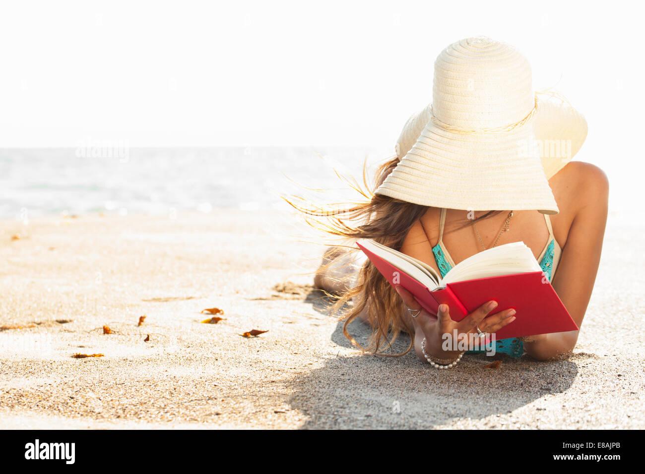 Giovane donna a prendere il sole e la lettura di un libro sul Beach, Malibu, California, Stati Uniti d'America Immagini Stock