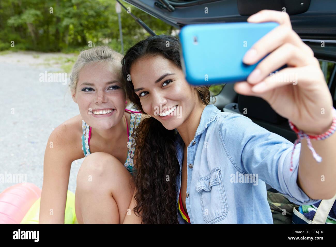 Gli escursionisti seduta in corrispondenza della parte posteriore della macchina prendendo selfie Immagini Stock