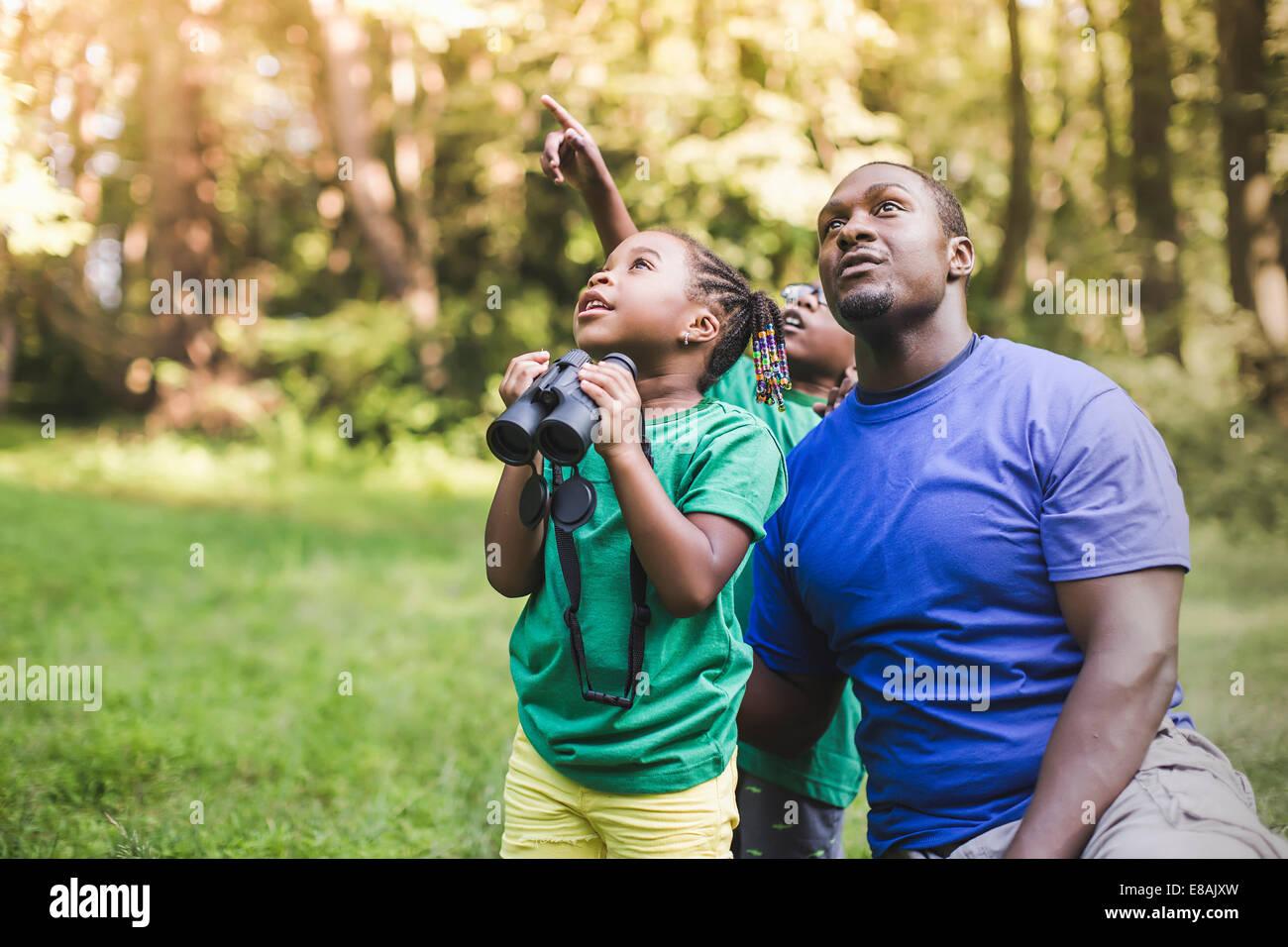 Giovane padre con il figlio e la figlia per il bird watching in eco forest camp Immagini Stock