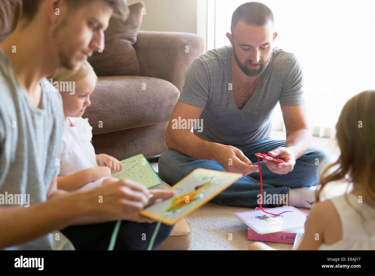 Giovane maschio e due figlie di threading libri foto seduta sul pavimento della camera Immagini Stock