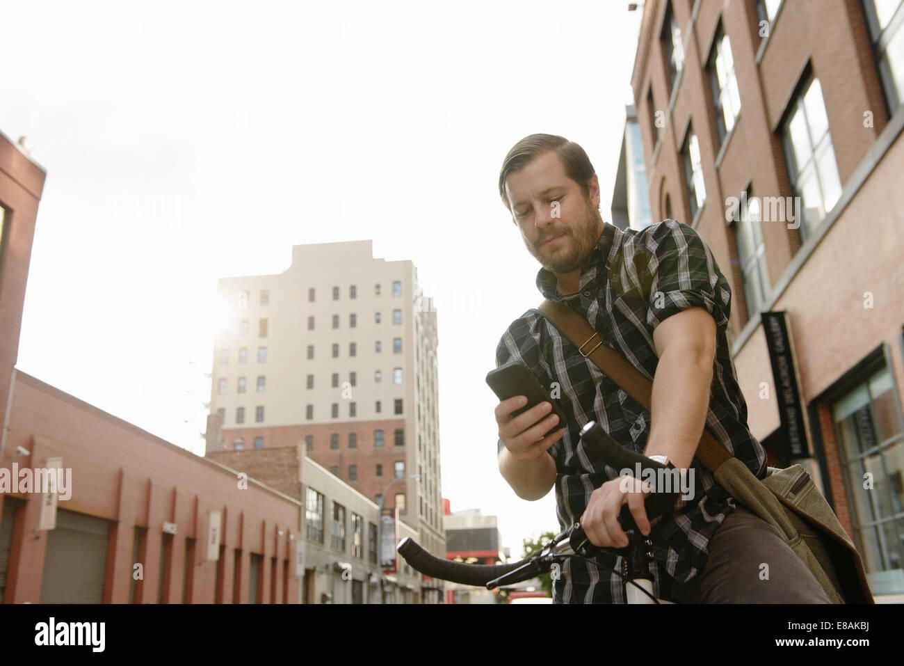 Ciclo maschio messenger direzioni di controllo sullo smartphone Immagini Stock