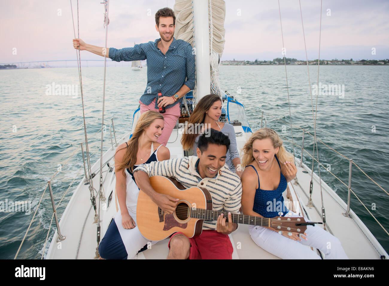 Amici sulla barca a vela, l'uomo a suonare la chitarra Immagini Stock