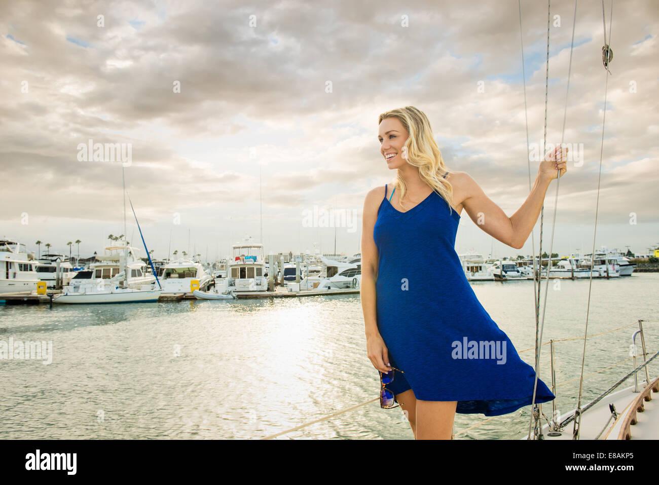 Giovane donna indossa vestito blu sulla barca a vela, ritratto Immagini Stock