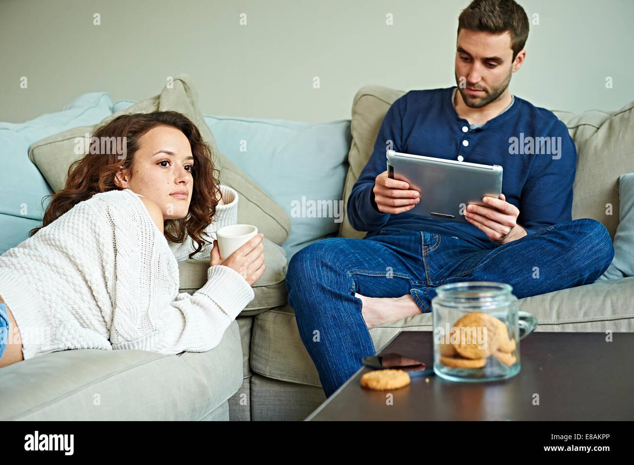 Giovane avente tranquillo il proprio tempo sul divano Immagini Stock