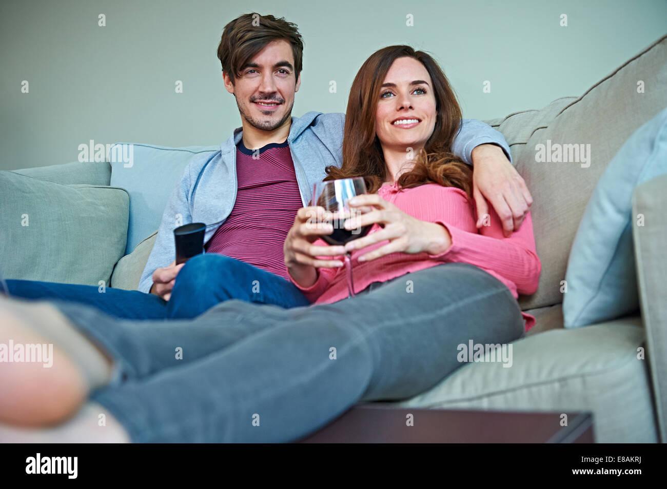 Giovane godendo di vino sul divano Immagini Stock