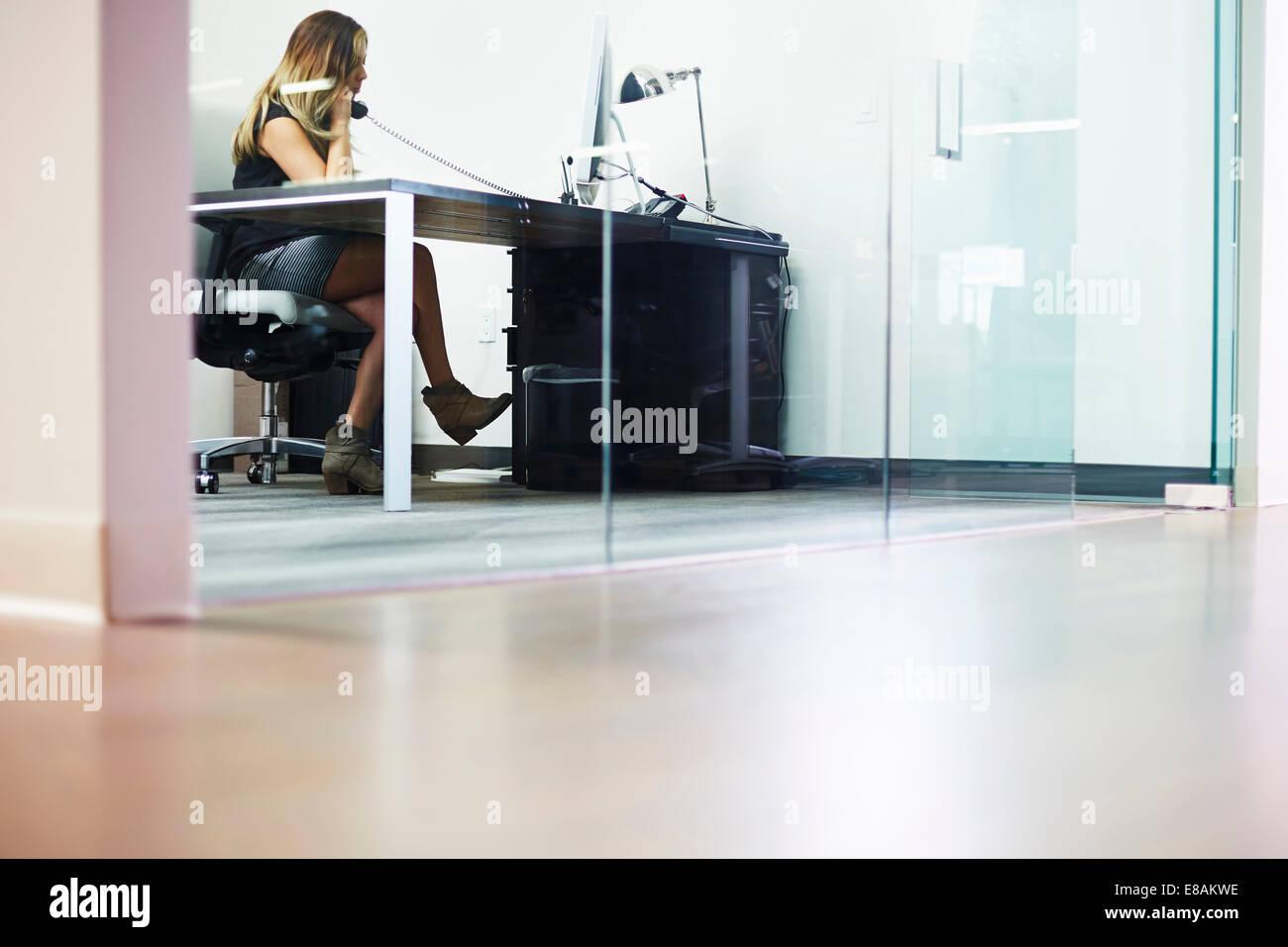 Giovane donna sul telefono in ufficio Immagini Stock
