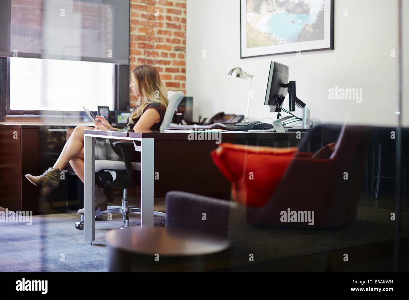 Giovane donna utilizzando tablet in ufficio Foto Stock