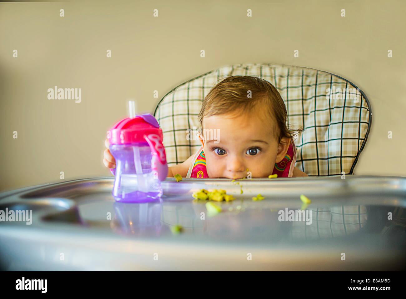 Ritratto di shy Baby girl in sedia alta Immagini Stock