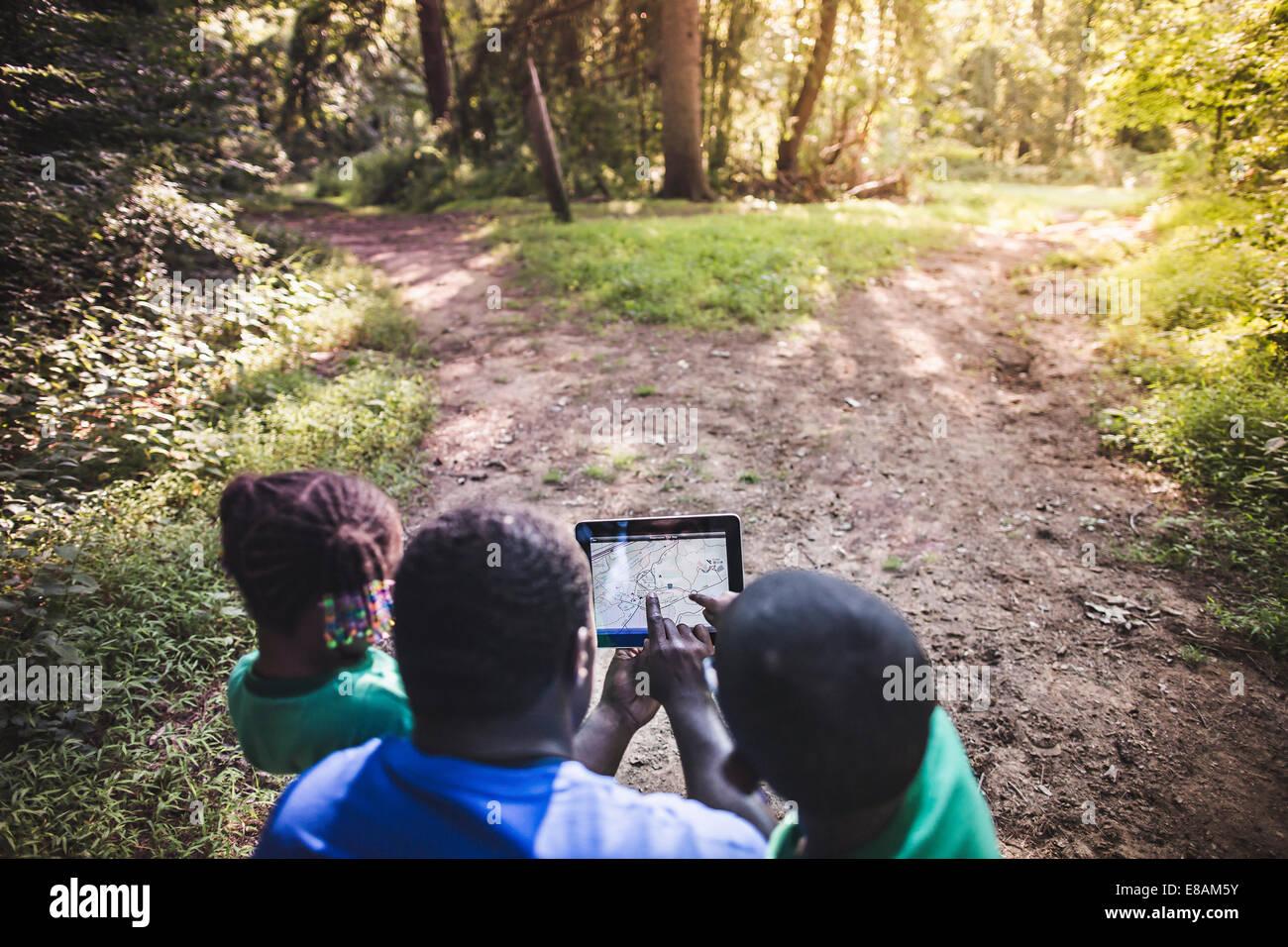 Padre con la figlia e il figlio la navigazione con tavoletta digitale nella foresta eco camp Immagini Stock