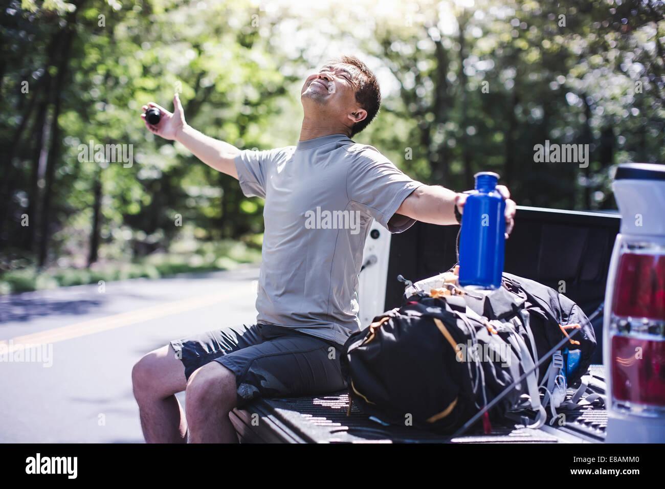 Coppia uomo seduto su pick up truck con braccia Immagini Stock