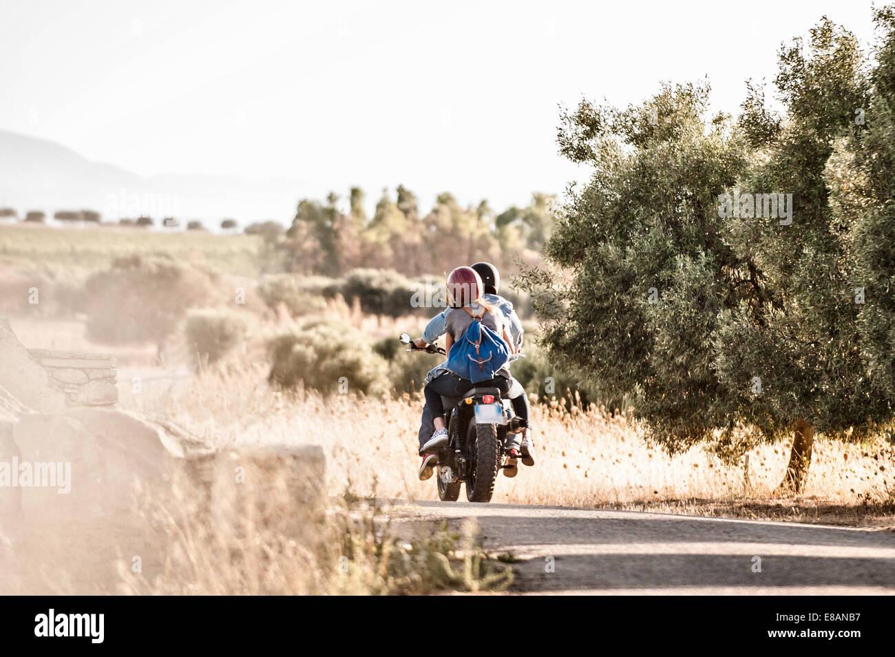 Vista posteriore della metà adulto giovane riding motociclo su polverosa strada rurale, Cagliari, Sardegna, Immagini Stock